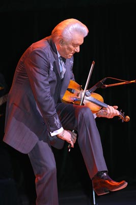 Tommy playing the fiddle behind his knee.