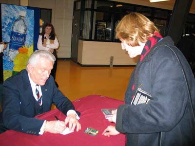 Tommy Hunter signing CDs for Linda at a table.