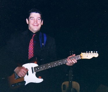 Steve Petrie posing with his guitar.