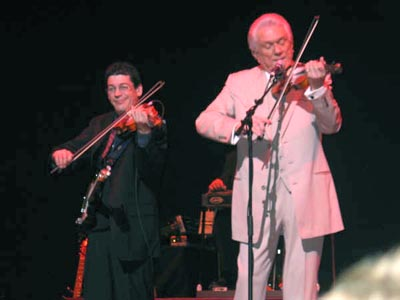 Tommy and Steve playing fiddle on stage.