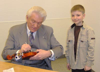 Tommy signing a young boy's fiddle