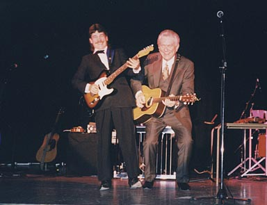 Tommy & Steve beside eachother on stage, smiling. Tommy is squatting and Steve is stretching upwards.