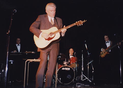 Tommy playing the guitar on stage with his band in the background.