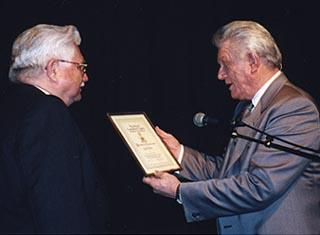 Tommy hunter receiving a certificate of appreciation from Geroge Lipinski.