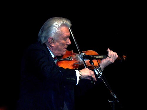 Tommy hunter playing the fiddle on stage.
