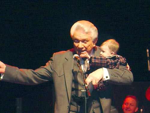 Tommy holding his granddaughter nicole on stage