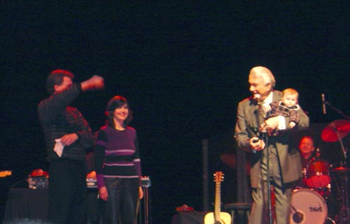 Tommy holding his granddaughter nicole on stage while her parents Greg and Sherry stand nearby.